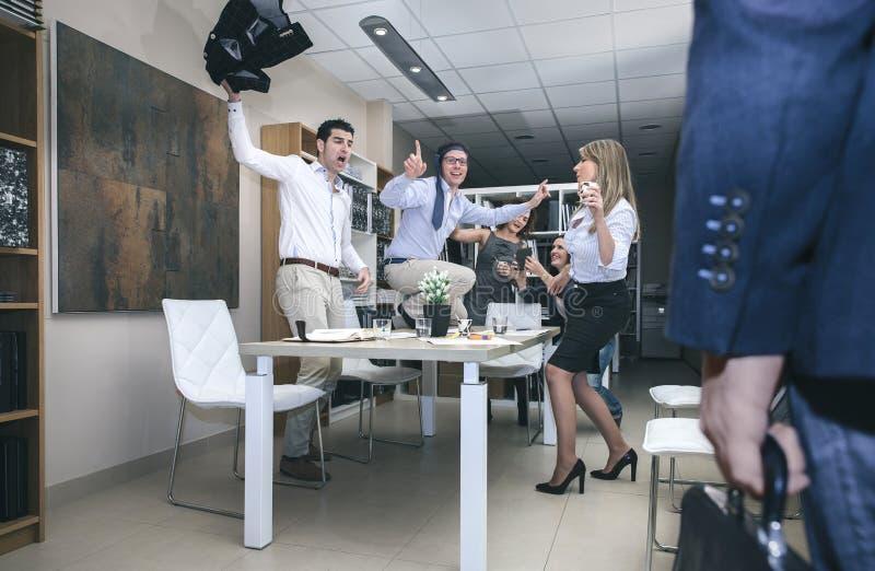 Chefe que chega ao escritório quando trabalhadores que dançam dentro foto de stock