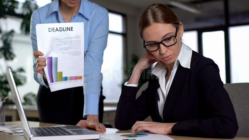 Chefe que discute o empregado inexperiente novo para a baixa avaliação e o fim do prazo faltado foto de stock