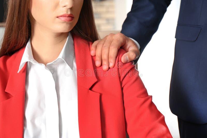Chefe que molesta seu secretário fêmea no escritório, close up imagem de stock