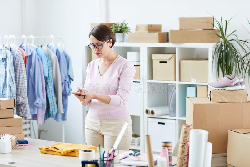 Chefen av online-casualwearen shoppar fotografera den vikta gula sweatern arkivfoton