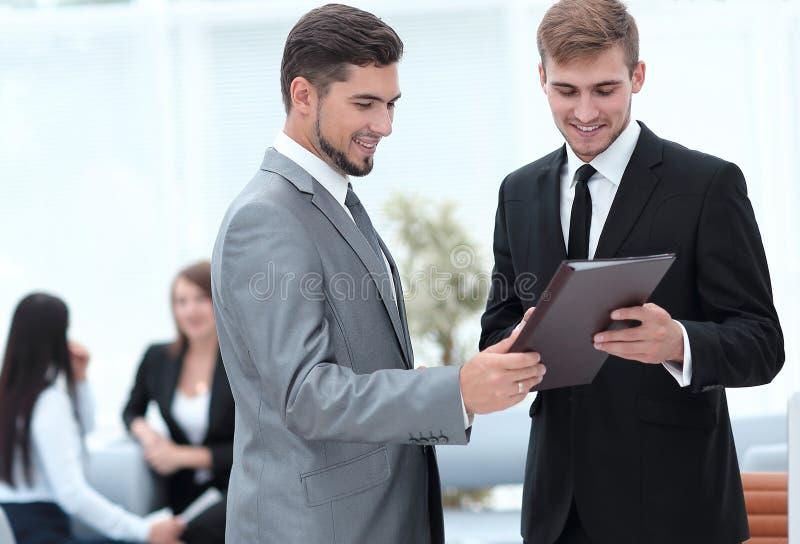 Chefen framför till anställd dokumenten i kontoret royaltyfri foto