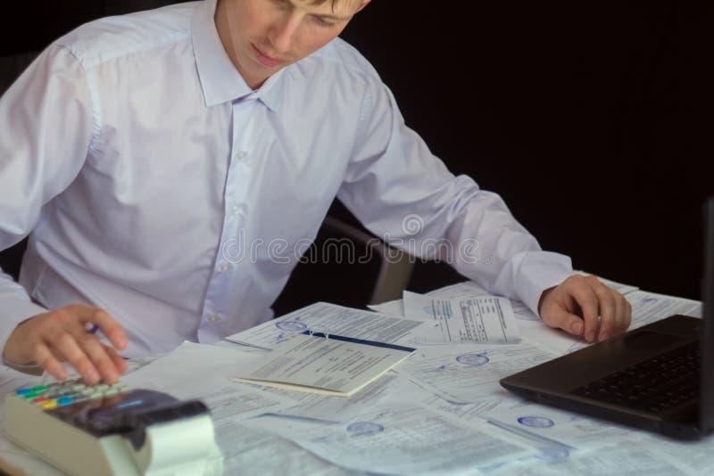 Chefen g?r rapporten och fyller in f?rklaringen Aff?rsman p? arbete i hans arbetsplats Ung grabb på tabellen med a royaltyfri foto