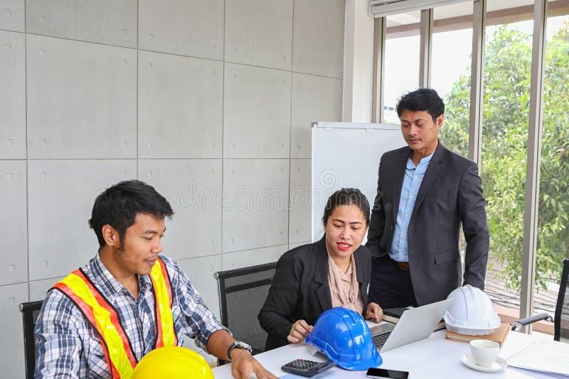 Chefen kontrollerar arbetet av teknikerlaget Planläggning av teknikerer och tekniker Tekniker- och arkitektplanläggning royaltyfria foton