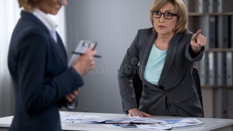 Chefen sparkar ut kvinnlig anställd från kontoret, avslutning av anställning royaltyfri foto