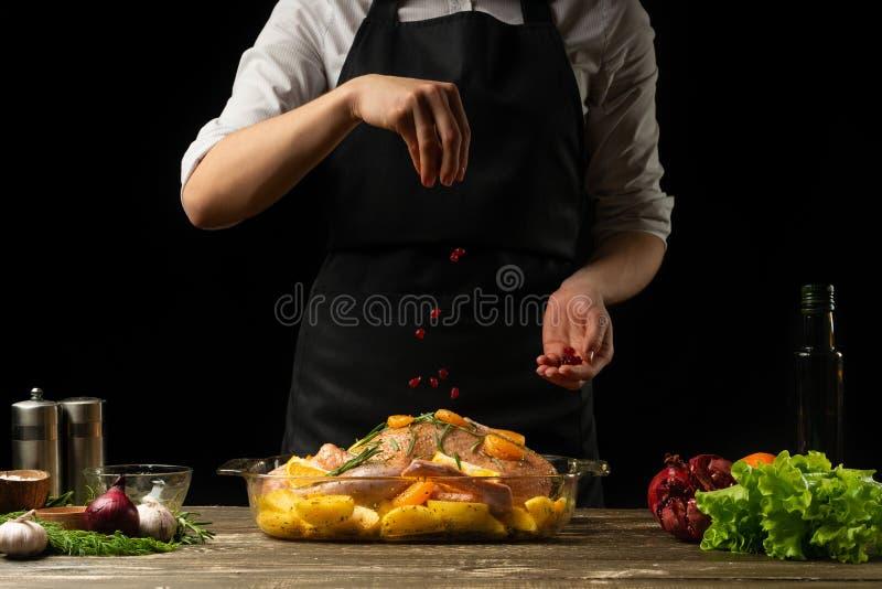 Chefente kochend, besprühen Sie mit den Körnern des Granatapfels eingefroren, horizontales Foto, schwarzer Hintergrund lizenzfreies stockbild