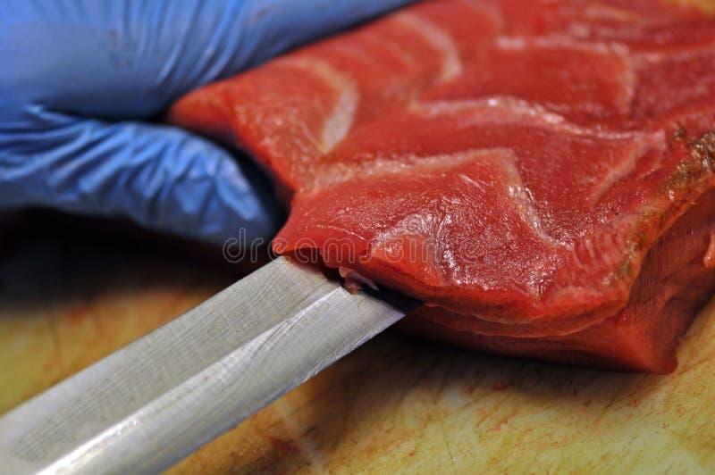 Cheff die rode tonijn in een restaurant snijden stock foto's