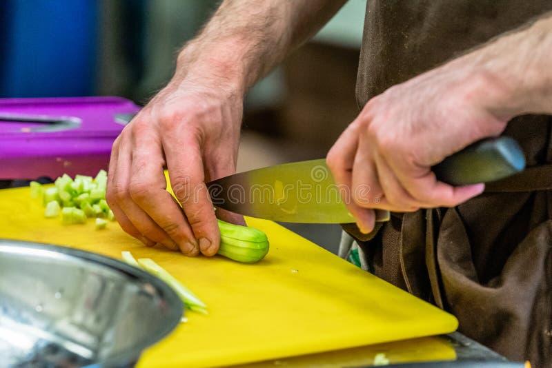 Cheff masculino que corta los pepinos conservados en vinagre para las ensaladas, casandose la comida fotografía de archivo libre de regalías