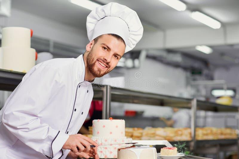 Chefgebäckmann, der Kuchen in der Küche tut lizenzfreies stockfoto