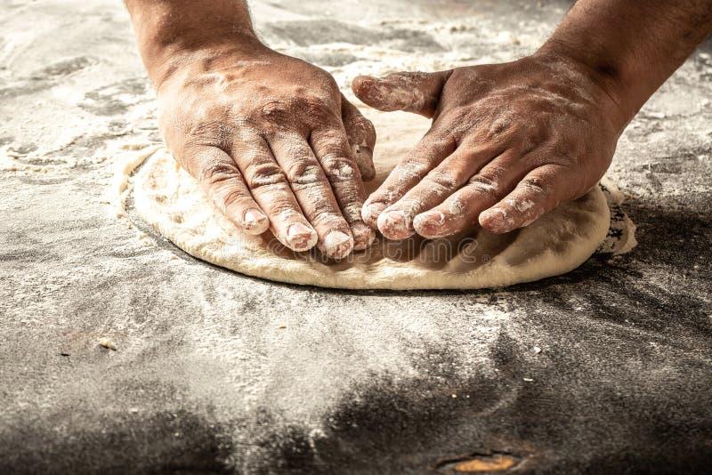 Chefhände, die Teig auf dunklem hölzernem Hintergrund kochen Mann, der Brotteig zubereitet Chef gießt Olivenöl über frischem Sala lizenzfreies stockfoto