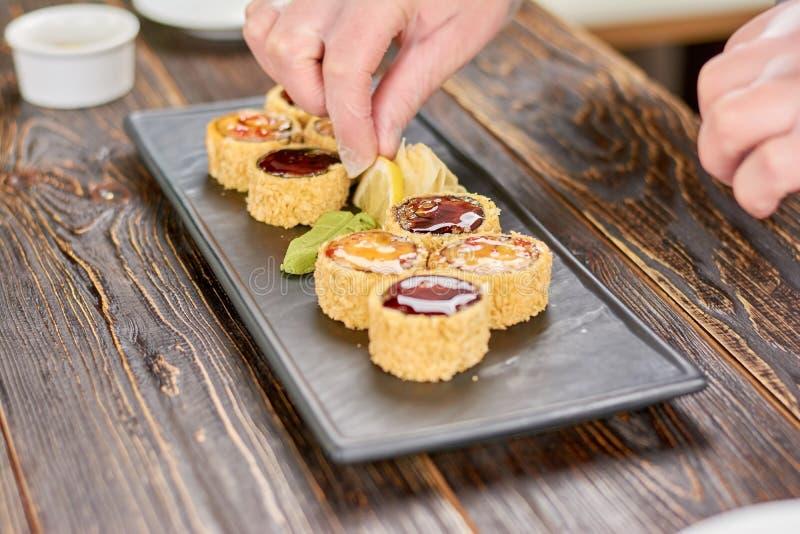 Chefhände, die Zitrone Sushirollen hinzufügen lizenzfreies stockfoto