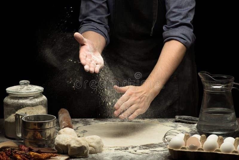 Chefhände klatschen Weizenmehl unter gerolltem Teig lizenzfreie stockfotografie