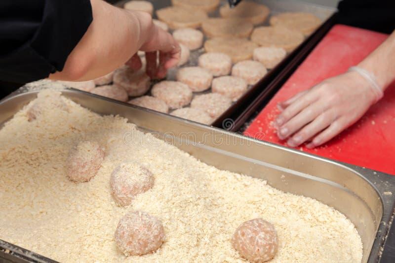 Chefh?nde, die, bildend, panierendes H?hnerkotelett mit Messer auf Berufsrestaurantk?che schaffen Schnelles Lebensmittelunternehm stockbild