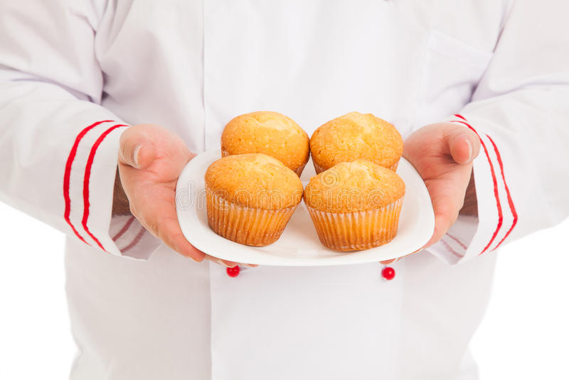 Chefhalteplatte mit 4 Muffins, die rote und weiße Uniform tragen lizenzfreie stockfotos