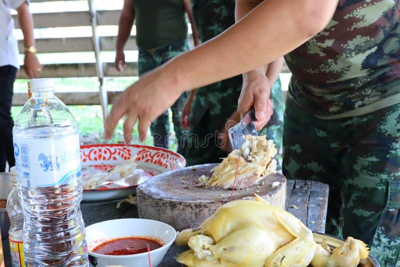 Chefhand, männlicher Soldat Is, das ein Messer verwendet, um Hühnerfleisch auf einem hölzernen hackenden Brett, thailändische Nah lizenzfreies stockfoto