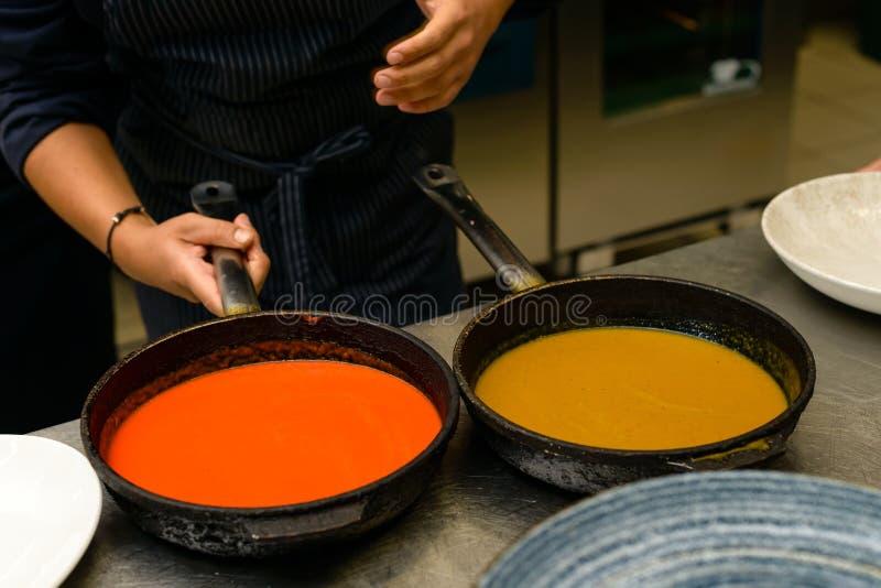 Chefkoch bereitet eine scharfe Soße in der Bratpfanne für eine köstliche Mahlzeit im Küchenrestaurant zu lizenzfreie stockfotos