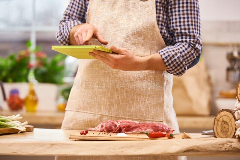 Chefmetzger, der Rezept mit digitaler Tablette in der modernen authentischen Küche vorbereitet stockbild