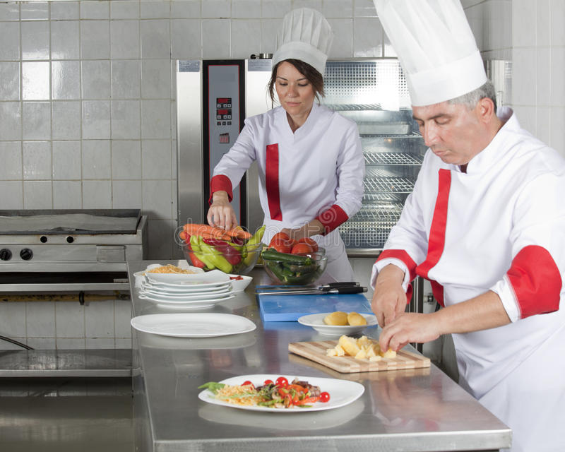 Chefs. Two chefs at work in a restaurant royalty free stock photos