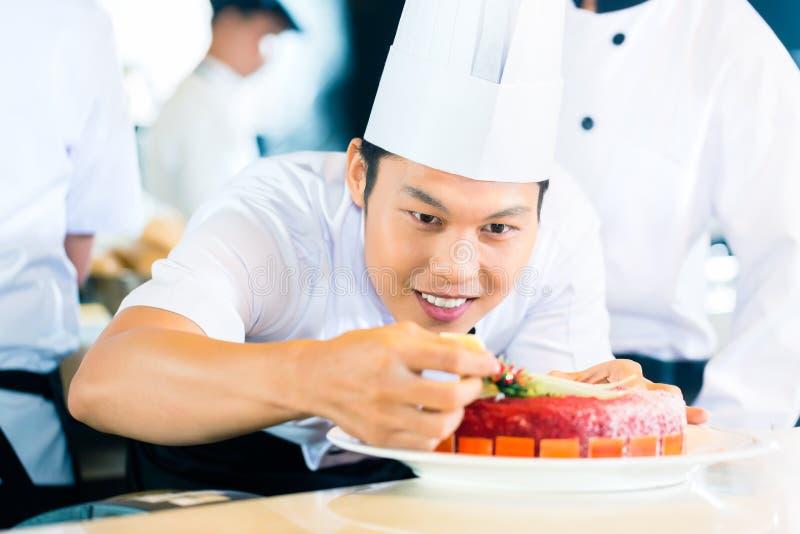 Chefs asiatiques faisant cuire dans le restaurant photographie stock
