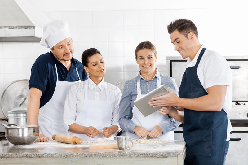 Chefs Checking Recipe On Tablet Computer In. Male and female chefs checking recipe on tablet computer while preparing pasta in commercial kitchen stock photography