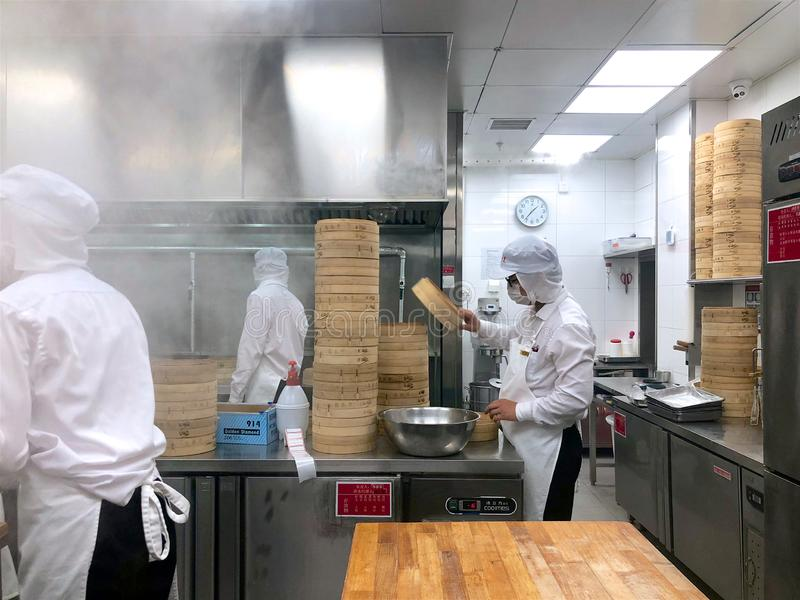 Chefs are cooking Chinese dumplings by the traditional bamboo steamers in a restaurant. stock photography