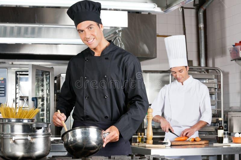 Chefs, die Lebensmittel in der Küche kochen stockfotografie