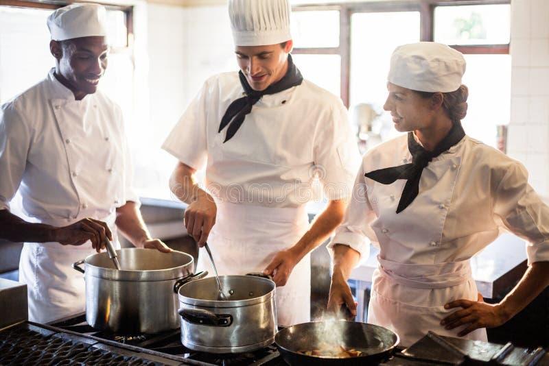 Chefs, die Lebensmittel am Ofen zubereiten lizenzfreie stockfotografie