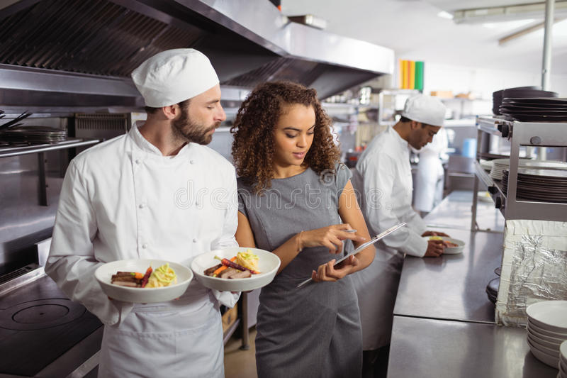 Chefs discussing menu on clipboard royalty free stock photo