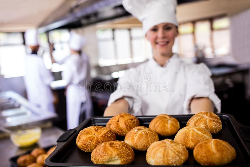Chefs féminins tenant le plateau de cuisson des petits pains de kaiser dans la cuisine photos libres de droits