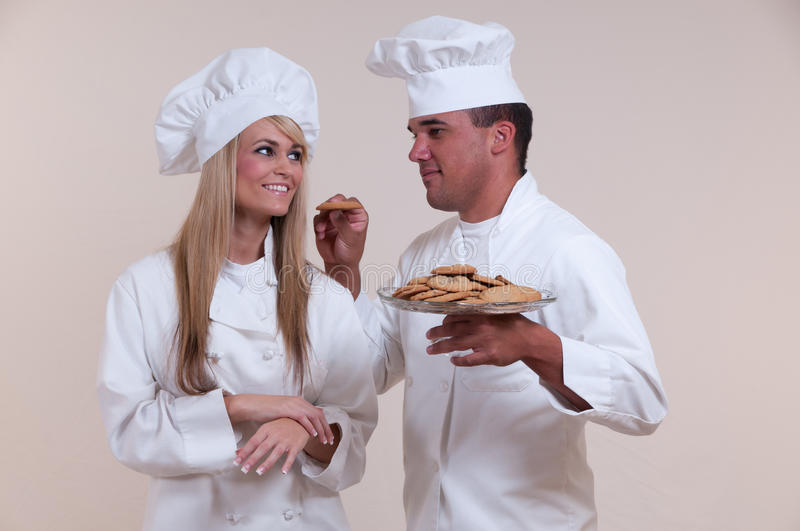 Chefs Friendship-comp. Close up relationship-comp photograph of two uniformed Chefs on a white background holding a glass serving platter of cookies royalty free stock photography