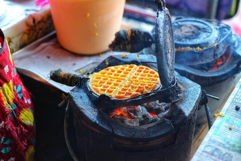 Chef& x27;s hands are making waffles with charcoal-iron turtle, traditional Thai street food. royalty free stock image