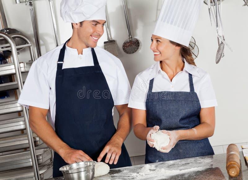 Chefs heureux malaxant la pâte dans la cuisine images stock