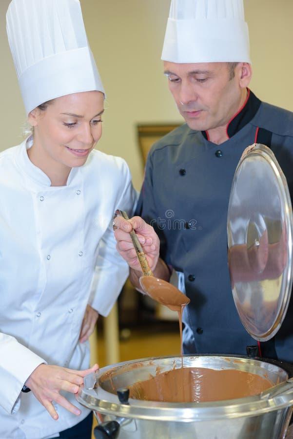 Chefs préparant l'écrimage de praline pour leurs pâtisseries délicieuses photos libres de droits