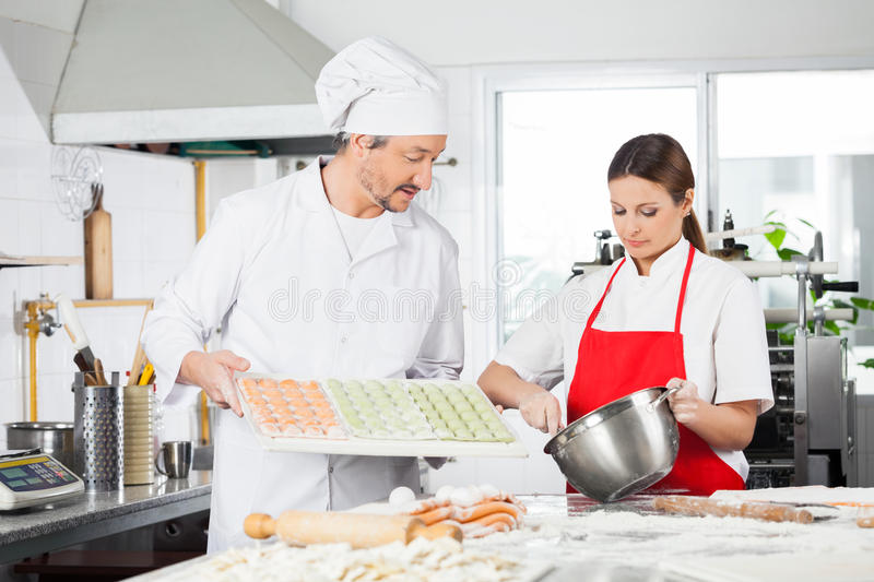 Chefs Preparing Ravioli Pasta At Kitchen Counter stock photo
