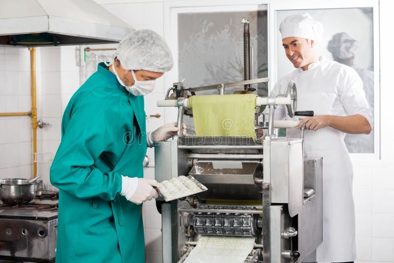 Chefs Preparing Ravioli Pasta In Machine royalty free stock photography