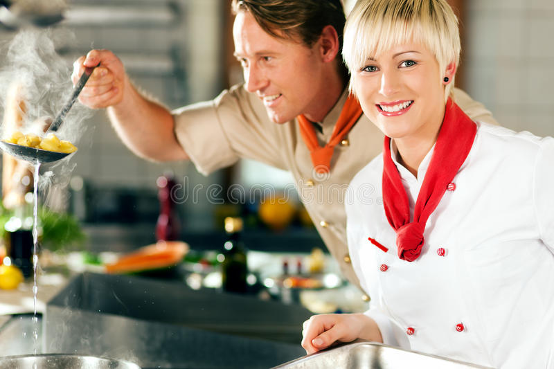 Chefs in a restaurant or hotel kitchen cooking. Two chefs in teamwork - man and woman - in a restaurant or hotel kitchen cooking delicious food, he is taking out royalty free stock photography