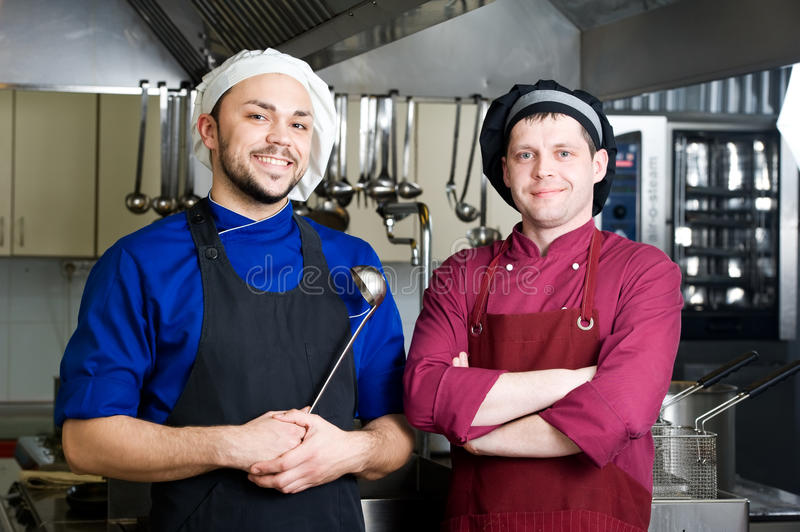 Chefs with scoop. Two smiley chefs in commercial kitchen royalty free stock images