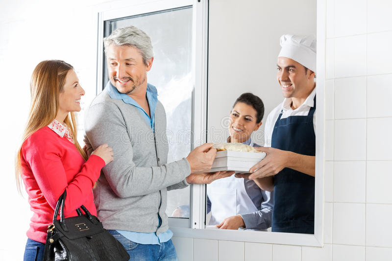 Chefs Selling Pasta Packets To Couple Through royalty free stock images