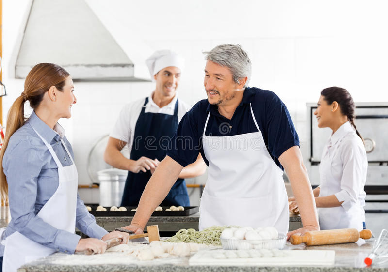 Chefs Talking While Preparing Pasta At Kitchen. Chefs talking while preparing pasta with colleagues working in background at commercial kitchen royalty free stock images