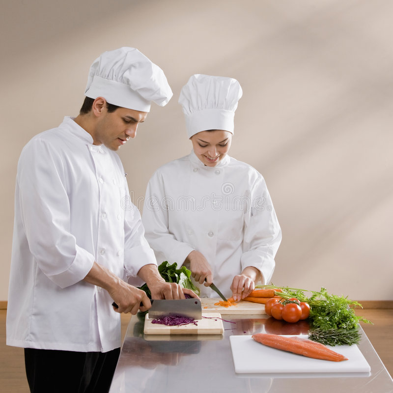 Chefs in toques preparing and chopping food. Chefs in toques and chef�s whites preparing and chopping fresh vegetables together stock photos