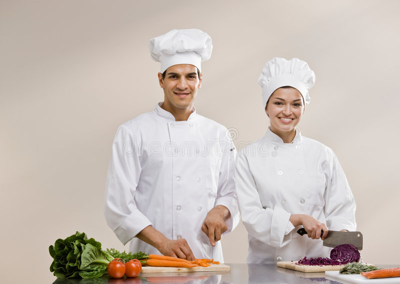Chefs in toques preparing and chopping food. Chefs in toques and chef�s whites preparing and chopping fresh vegetables together royalty free stock photo