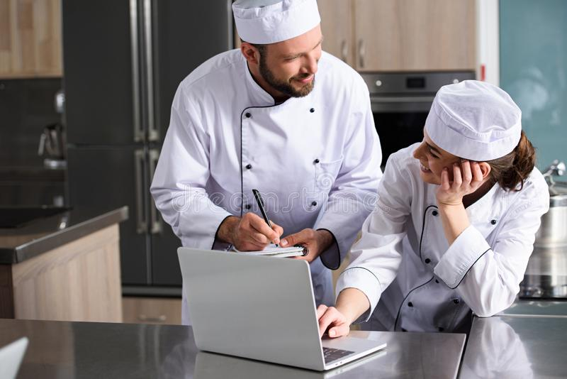 Chefs using laptop at restaurant kitchen. And searching recipe royalty free stock images