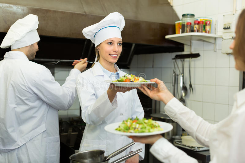 Chefs and waitress at kitchen. Team of two chefs and waitress at the work at restaurant kitchen royalty free stock photos