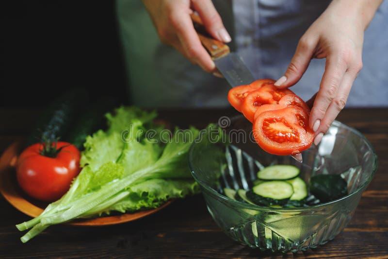 Chefschnitte mit einem Messer eine Tomatennahaufnahme lizenzfreie stockfotografie