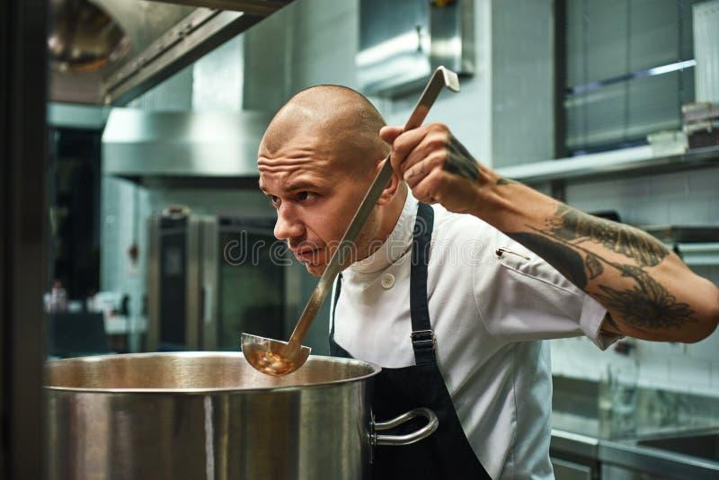 Cheire o cozinheiro chefe novo e considerável tão bom com tatuagens em seus braços que provam e que cheiram uma sopa em uma cozin fotos de stock royalty free