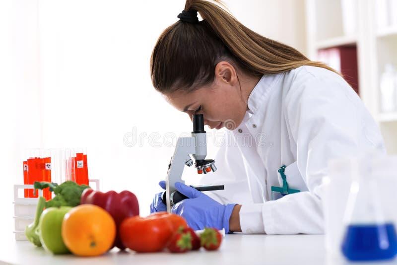 Cheking在专业实验室的食品卫生有显微镜的 图库摄影