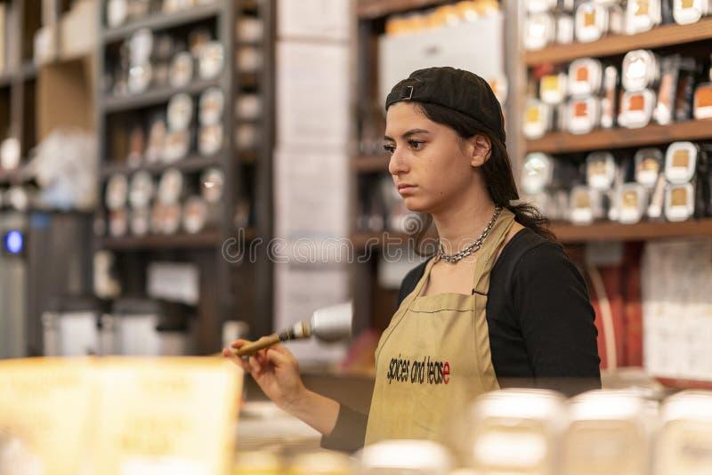 CHELSEA MARKNAD, NEW YORK CITY, USA - 21 Juli 2018: Försäljningskvinna i kryddalager i Chelsea Market arkivbilder