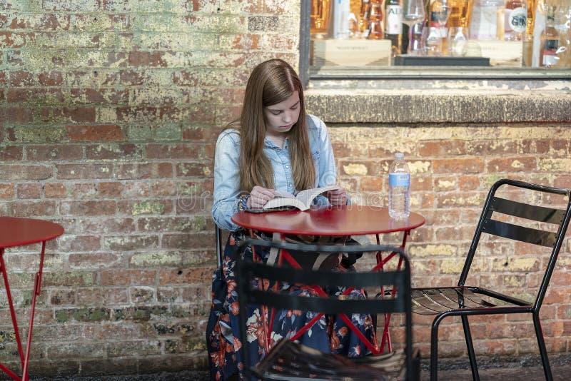 CHELSEA MARKT, de STAD van NEW YORK, de V.S. - 21 Juli 2018: Het jonge boek van de meisjeslezing in koffie royalty-vrije stock foto
