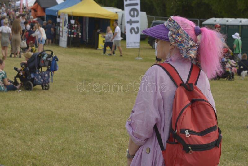 Cheltenham, Ηνωμένο Βασίλειο - 22 Ιουνίου 2019 - γυναίκα με τη ρόδινη τρίχα, από πίσω ετήσιο φεστιβάλ ζεστού αέρα baloon στην Αγγ στοκ εικόνες