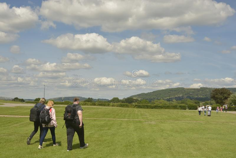 Cheltenham, Förenade kungariket - Juni 22, 2019 - morgrupp människor som går på den gröna dalen och blå himmel med vita moln i En royaltyfri bild