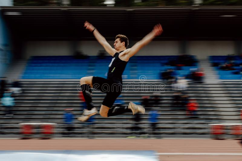 Long jump male athlete blurred motion. Chelyabinsk, Russia - June 2, 2018: long jump male athlete blurred motion during UrFO Championship in athletics royalty free stock image